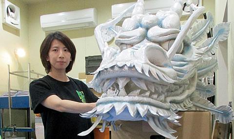 常にタイトな制作スケジュールの中でがんばる中堅女性社員。手にしているのは『超歌舞伎』の舞台で使われた龍の頭の小道具