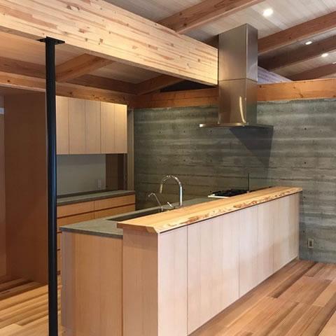 木材の質感が美しいキッチン、耐久性が必要なカウンターには無垢材や人工素材(ベクトン)を組み合わせ、素材の長所を活かす